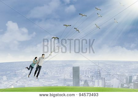 Young Couple Is Flying By Holding Birds