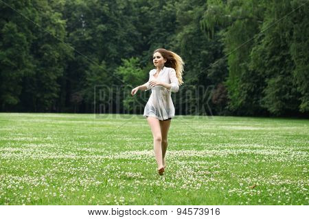 Young beautiful girl in the white shirt is running on the green field in summer park