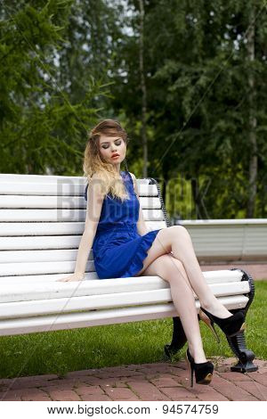 Young beautiful blonde girl in blue dress sitting on a bench in summer park
