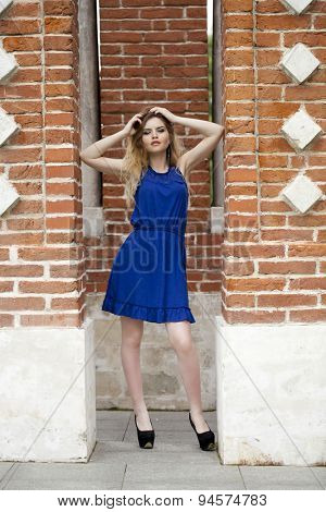 Portrait in full growth, attractive young blonde woman in blue dress against the brick wall