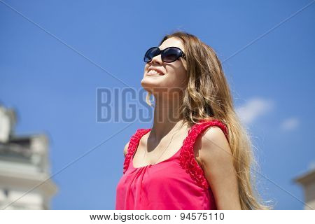 Young beautiful blonde woman in sunglasses, against the blue sky on a sunny day