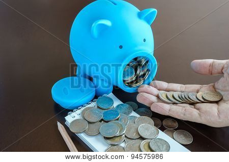 Money In Hand From Saving In Piggy Bank