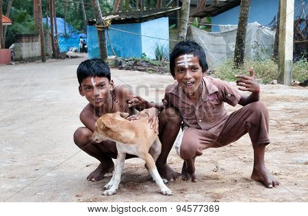 Two Indian Boys With Dog On The Street In Fishing Village