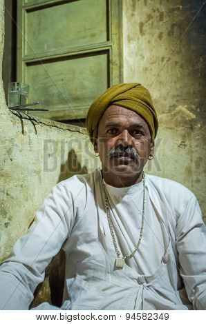 GODWAR REGION, INDIA - 12 FEBRUARY 2015: Indian man dressed in traditional clothes sits on kitchen floor next to window.