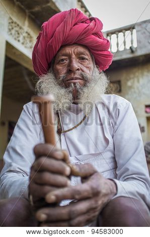 GODWAR REGION, INDIA - 12 FEBRUARY 2015: Elderly Rabari tribesman with traditional turban, clothes and long beard holds chillum. Rabari or Rewari are an Indian community in the state of Gujarat.