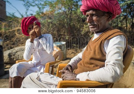 GODWAR REGION, INDIA - 13 FEBRUARY 2015: Elderly Rabari tribesman sits with neighbour who smokes chillum. Rabari or Rewari are an Indian community in the state of Gujarat.