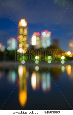 Abstract blur bokeh city lights during twilight, with water reflection