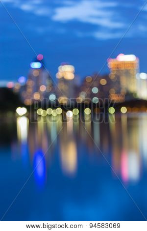 City skyline bokeh lights during twilight with water reflection