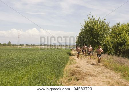 Men With Bare Breast Running In A Field
