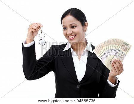Businesswoman Holding House Key And Currency Notes