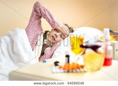 Girl With High Temperature Lying In Bed And Looking On Tea