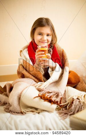 Cute Girl Covered In Blanket Drinking Hot Tea With Lemon In Bed