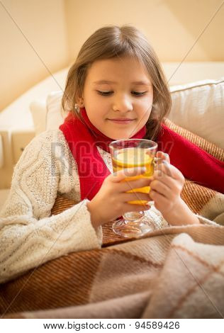 Cute Girl Lying In Bed And Holding Cup Of Tea With Lemon