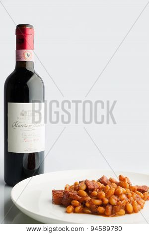 Baked beans in tomato sauce with red wine bottle on white