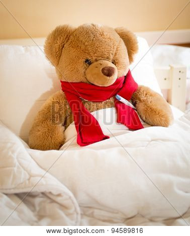 Closeup Of Teddy Bear In Red Scarf Lying In Bed