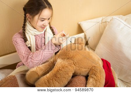 Girl Playing With Brown Teddy Bear And Making Injection