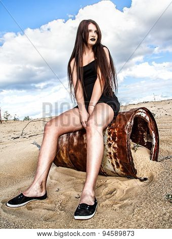 Young Woman Sitting On A Rusty Barrel