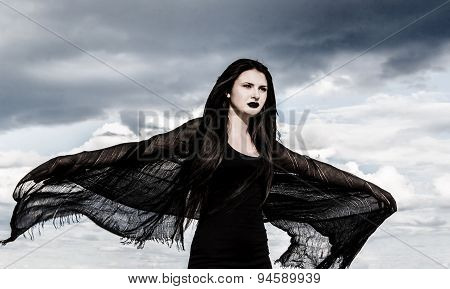 Young Woman In A Black Fluttered Clothes