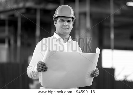 Black And White Portrait Of Foreman Posing With Documents And Blueprints