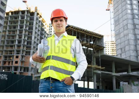 Site Manager Posing With Blueprints Against Unfinished Building