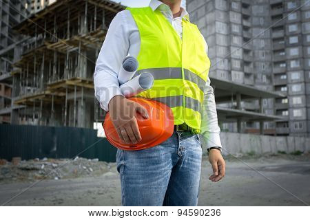 Architect In Jacket Posing With Red Helmet At Construction Site