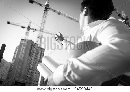 Black And White Closeup Of Engineer Pointing At The Building