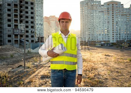 Portrait Of Engineer Posing With Blueprints Against Building Site