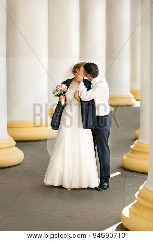Groom Covering Brides Shoulders With Jacket And Kissing Her