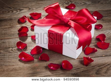Gift Box And Rose Petals On The Old Wooden Boards