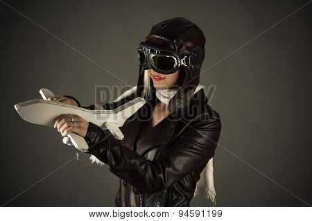 woman in aviator hat standing with toy airplane