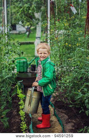 Child in Greenhouse. Garden. Vegetables. Outdoors portrait