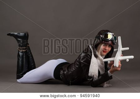 sexy young woman in aviator hat lying on the floor with toy airplane in hands