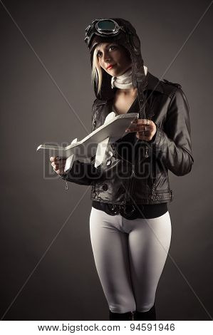 sexy woman in aviator hat standing with toy airplane in hand