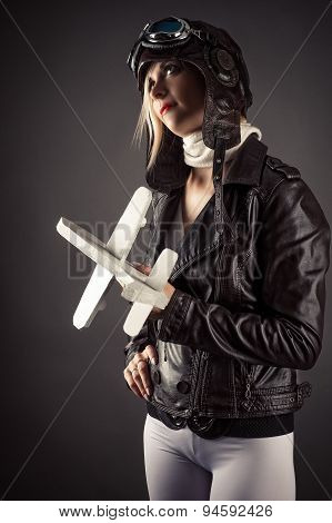 woman in aviator hat standing with toy airplane in hand