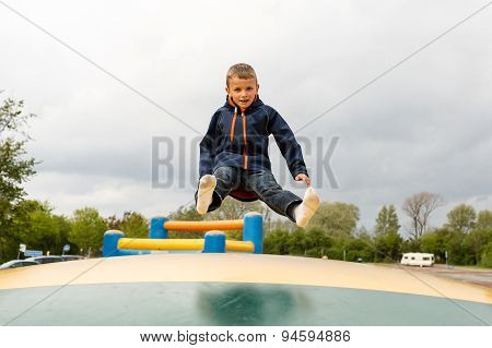 Boy On Trampoline At Playground