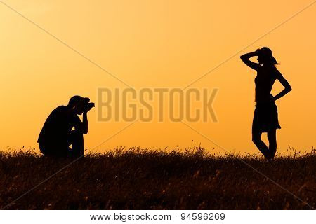 Silhouette of a man photographing woman