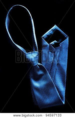 Closeup detail of blue tie for dressing up with suit and white shirt