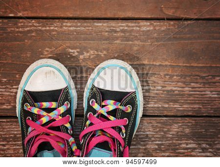 a wide angle photo of a pair of generic looking shoes like converse sneakers with pink shoe laces on a vintage wooden background