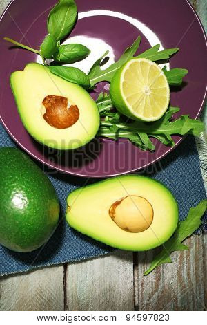 Sliced avocado, arugula and lemon lime on wooden background