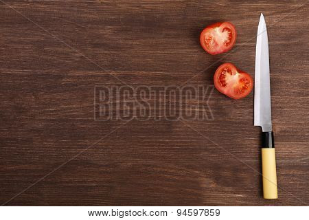 Halves of tomato with knife on wooden background