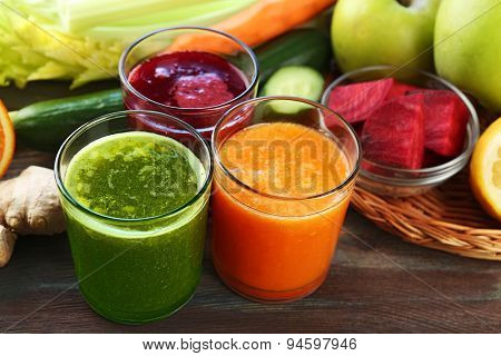 Assortment of healthy fresh juices on wooden table background