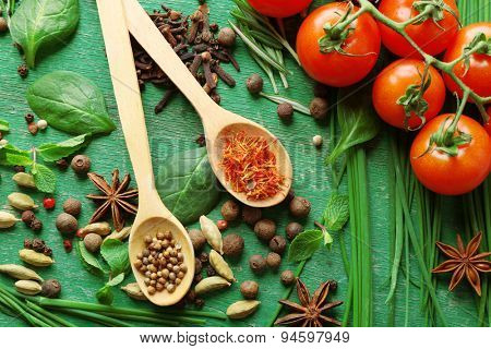Tomatoes with wooden spoons with fresh herbs and spices on wooden background