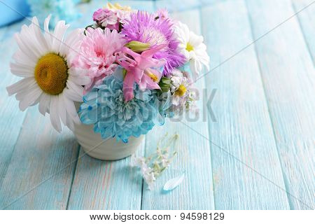Beautiful bright bouquet in vase on wooden background