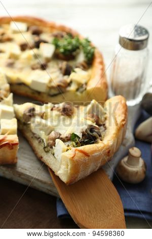 Cheese pie with mushrooms, herbs and sour creme, on napkin, on wooden table background
