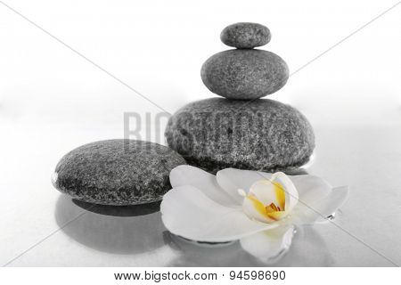 Stack of spa stones with orchid flower isolated on white