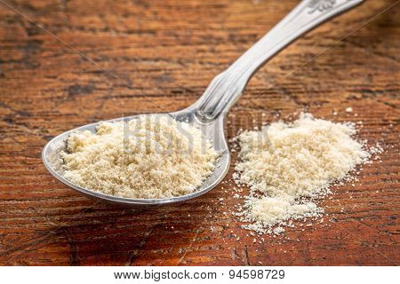 tablespoon of whey protein powder against rustic scratched wood background