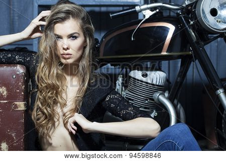 Stylish Woman In Garage With Suitcase