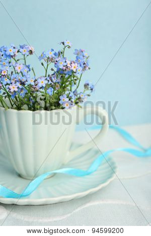 Forget-me-nots flowers in cup, on blue background