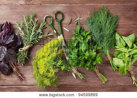Fresh garden herbs over wooden table. Top view