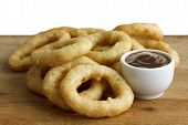 stock photo of dipping  - Heap of deep fried onion or calamari rings with barbecue dip on wood board - JPG